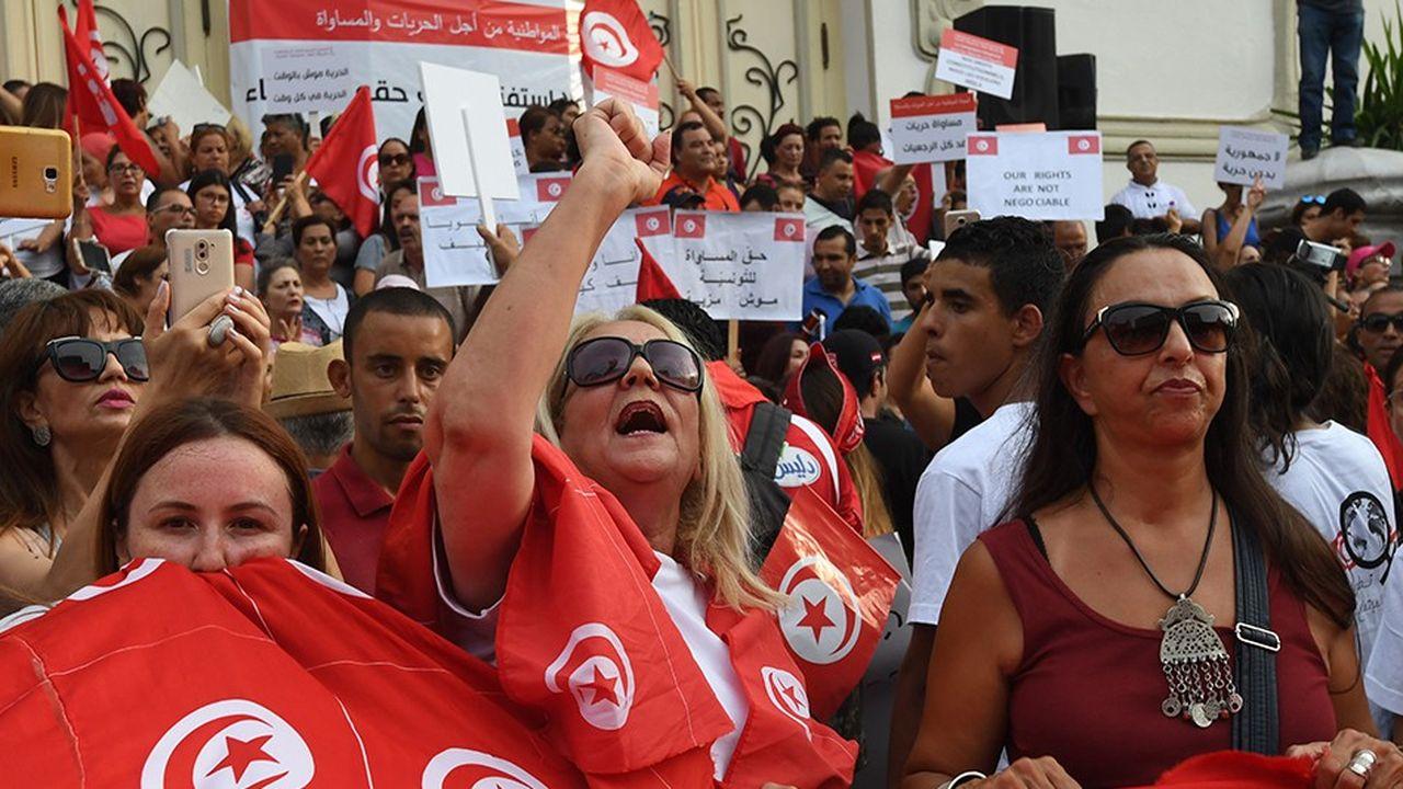 Des femmes brandissent le drapeau tunisien durant une manifestation lors de la Journée de la femme, 62 ans après le code personnel qui leur accordait des droits sans précédent dans un pays arabe.