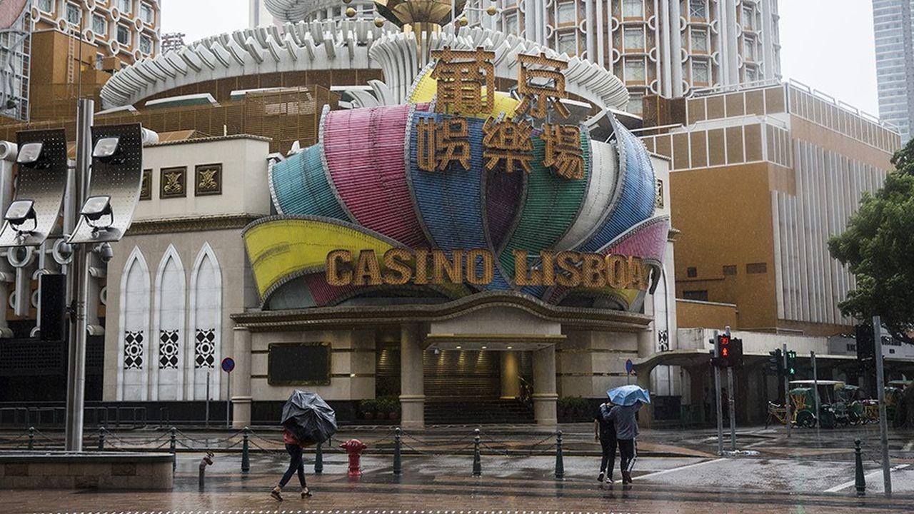 Des piétons bravant la pluie dimanche 16septembre devant le Casino Lisboa, l'un des plus emblématiques de Macao, à l'approche du typhon Mangkhut