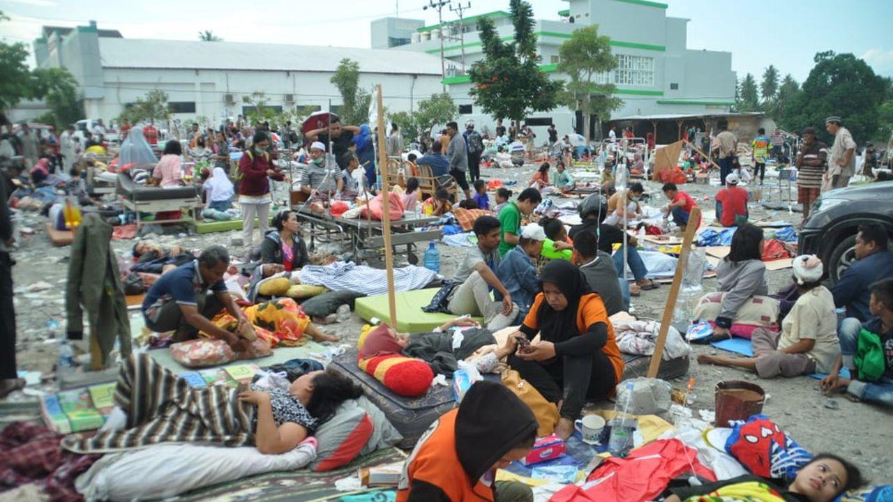 Des membres d'une équipe médicale s'occupent, en urgence, des blessés à l'extérieur d'un hôpital de la ville de Palu après le séisme et le tsunami qui a touché l'île des Célèbes en Indonésie.
