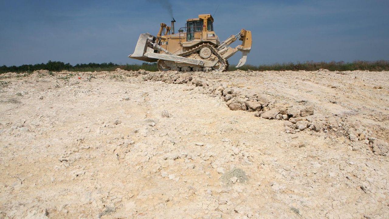 Carriere d'extraction du calcaire, un Buldozer Caterpillar extrait la matiere premiere