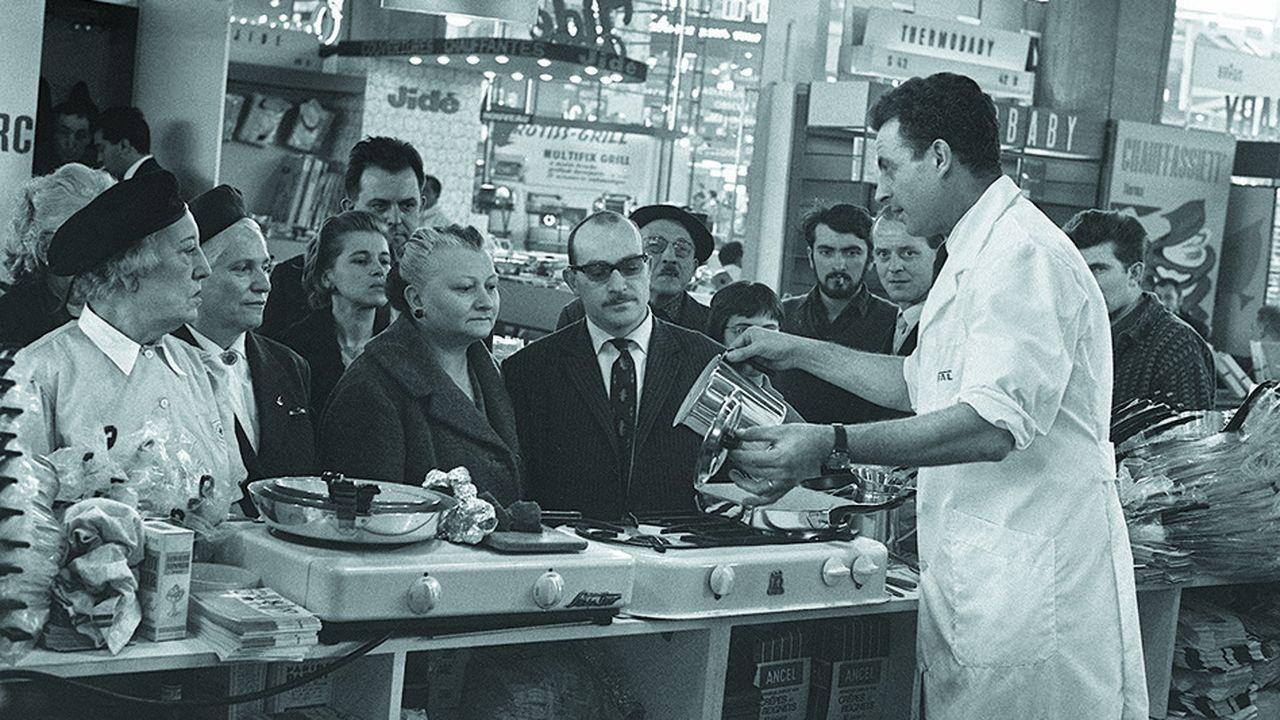 Des visiteurs se pressent autour du démonstrateur d'un nouvel appareil électroménager à Paris, le 27 février 1964, lors du salon des arts ménagers au palais de la Défense.