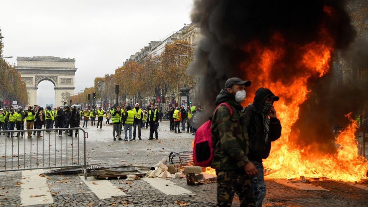 Sur les Champs-Elysées, des 'gilets jaunes' construisent une barricade avec des éléments de mobilier urbain, des chaises et tables de café.