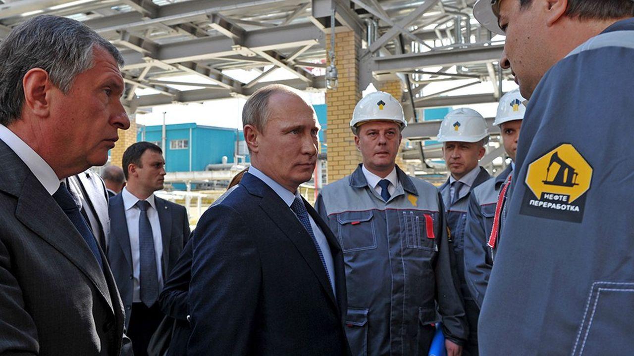 Vladimir Poutine (ici avec le président de Rosneft Igor Setchine, à gauche), doit convaincre les producteurs de pétrole russes de réduire leur production.