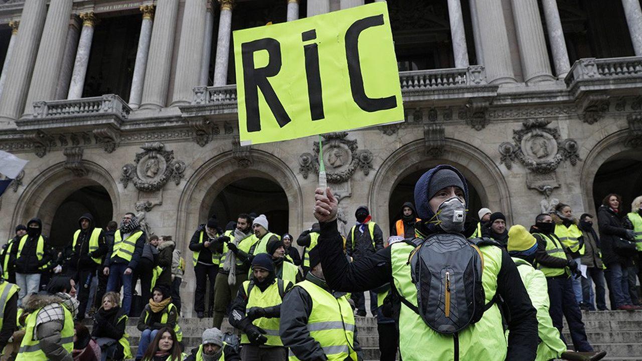 Samedi 15décembre à Paris, devant l'Opéra Garnier, des «gilets jaunes» brandissent une pancarte demandant l'instauration du référendum d'initiative citoyenne (RIC).