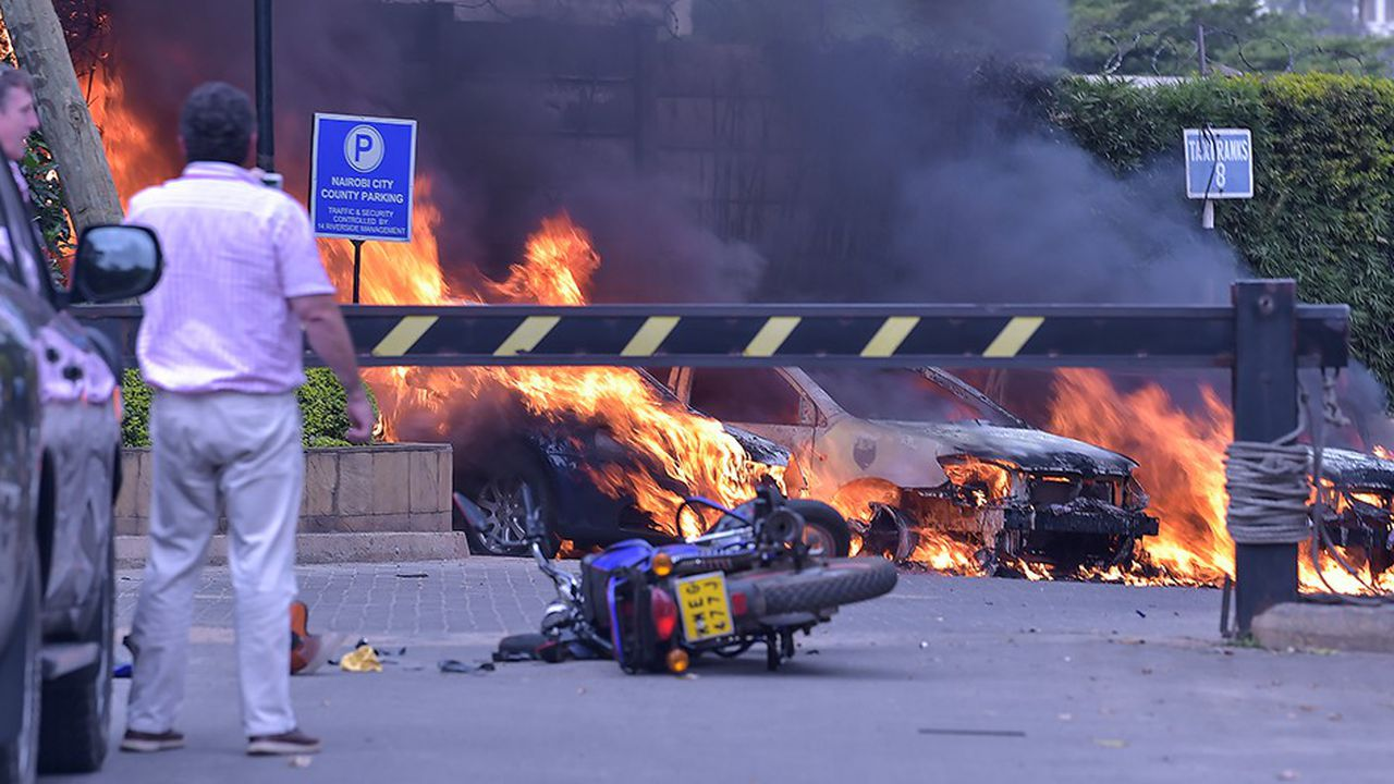 Deux hommes contemplent les débris de véhicules après l'explosion déclenchée au début de l'attaque terroriste de mardi à Nairobi, entendue à 5 kilomètres à la ronde.