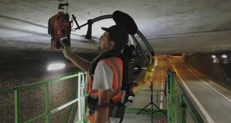 Les exosquelettes d'Exhauss, portés comme un sac à dos, ont été utilisés sur le chantier d'un tunnel de l'autoroute A72 afin de faciliter le percement au plafond des milliers de trous nécessaire au remplacement de lampes.