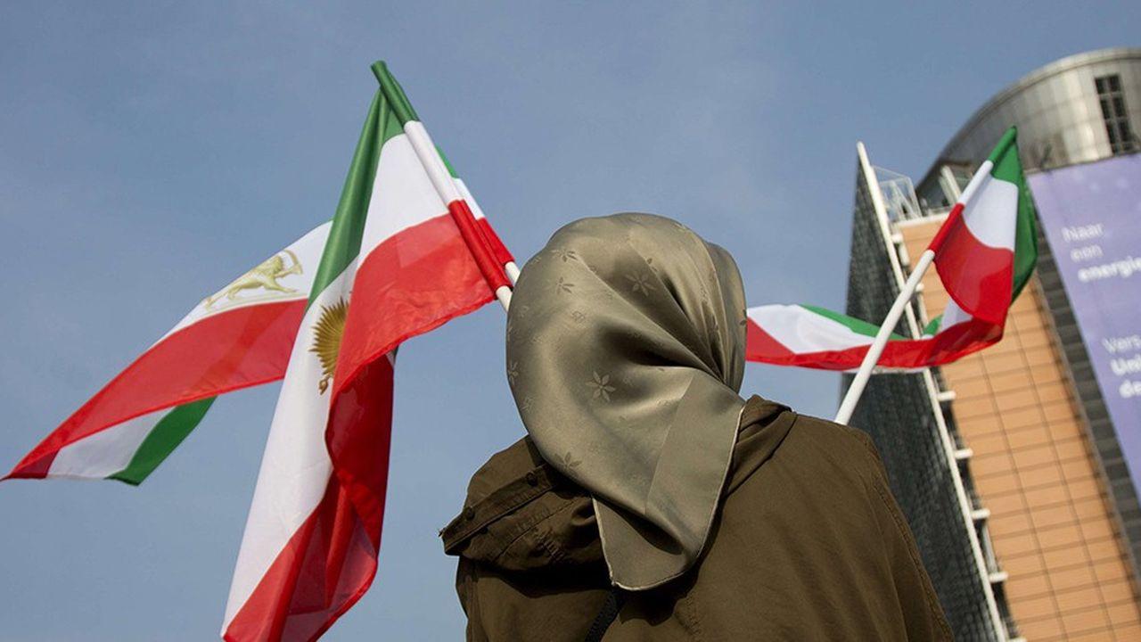 Une femme agite des drapeaux iraniens à Bruxelles, alors que des négociateurs européens et iraniens mettaient au point en 2015 un accord visant à limiter les capacités nucléaires de l'Iran en échange d'une levée progressive des sanctions. Un traité que Donald Trump s'est empressé de dénoncer.