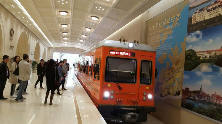 A bord d'un petit train rouge semblant descendre des montagnes suisses, visiteurs et employés de Huawei voient défiler en neuf minutes douze fausses villes d'inspiration européenne
