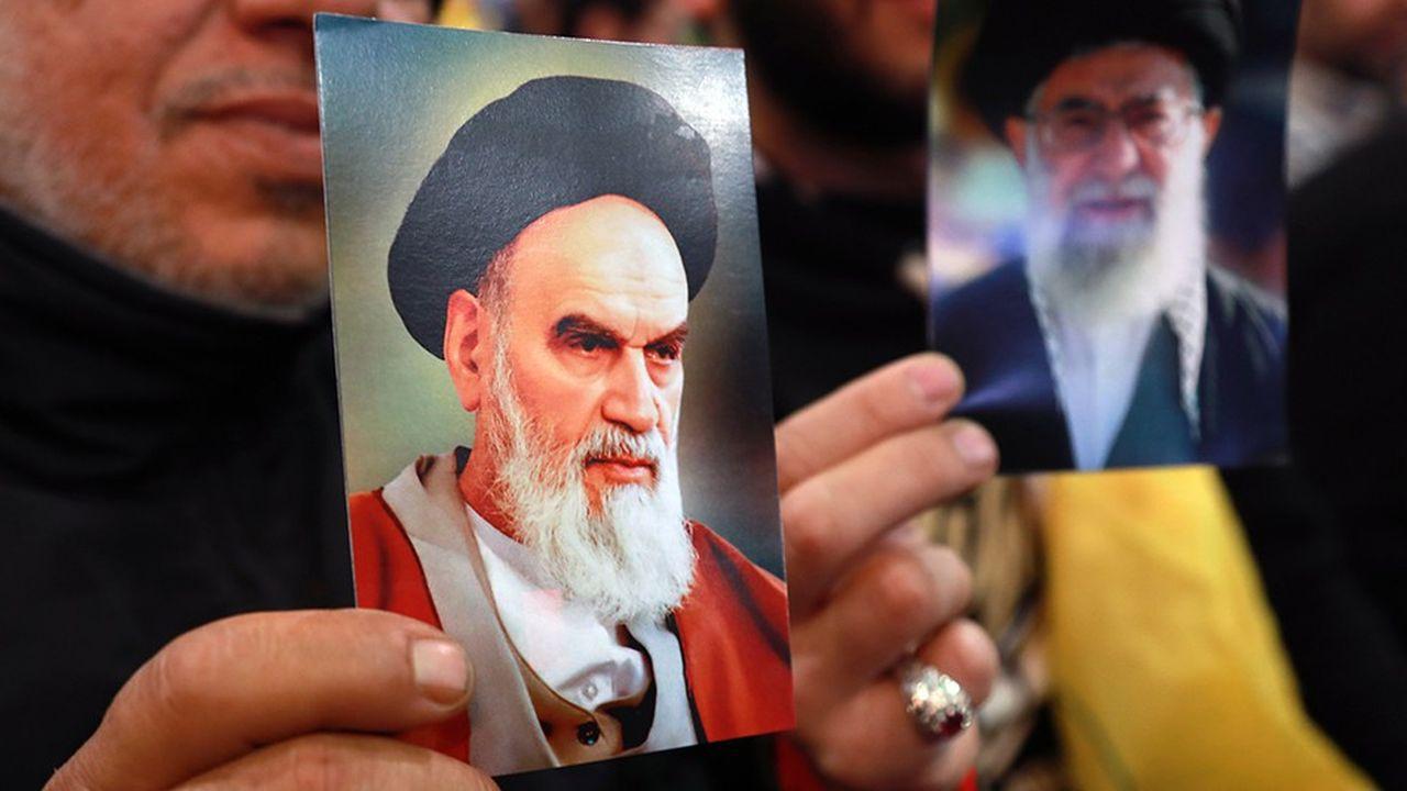 Des supporters du Hezbollah brandissent une photo de l'ayatollah Khomeiny et une autre de l'actuel guide suprême, Ali Khamenei.