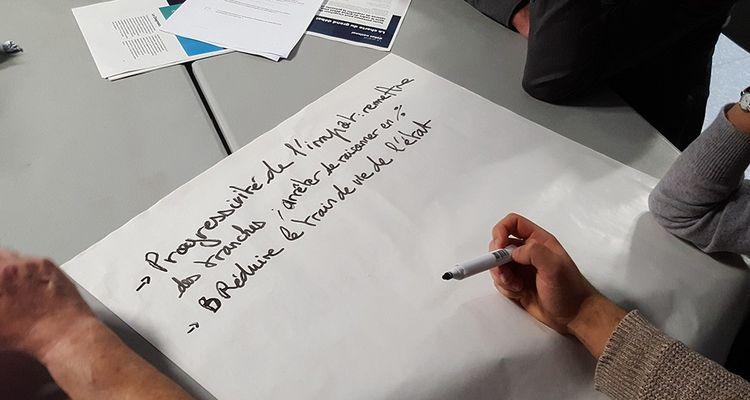 La réunion s'est déroulée par table de 8 à 10 sur chaque thème du grand débat. Les règles sont strictes : un modérateur par table et 20 minutes de discussions avant de coucher les propositions sur une grande feuille de papier.