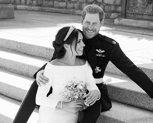 Le duc et la duchesse de Sussex pendant leur première séance de pose, après leur mariage. La jeune femme porte l'un des diadèmes de la reine Mary, arrière-grand-mère de son mari. Elle y a ajoué un bracelet Reflection et des boucles d'oreilles Galanterie en or gris et diamants Cartier.