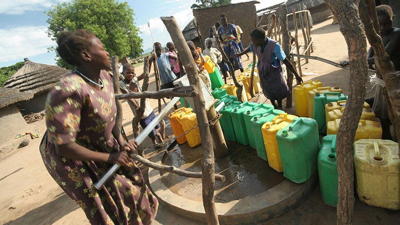 Une femme puise de l'eau dans un camp de réfugiés au nord de Kampala (Ouganda). Une corvée ruineuse en temps, à cause notamment des longues files d'attente, et qui pénalise la pratique d'autres activités indispensables au développement de populations en situation de détresse.