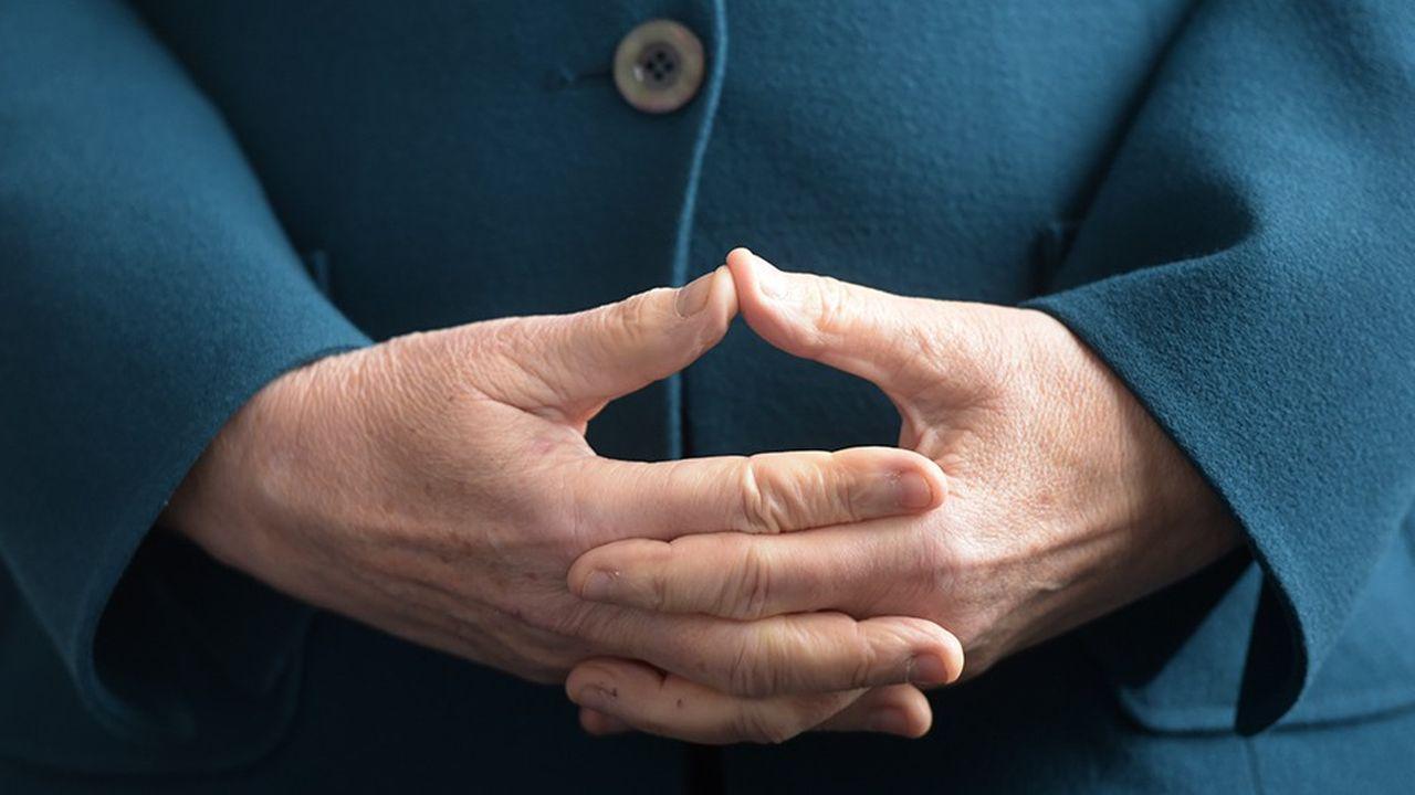 La chancelière allemande Angela Merkel, qui a l'habitude de former un losange avec ses mains, se montre attentiste à l'égard du projet de fusion entre Deutsche bank et Commerzbank.