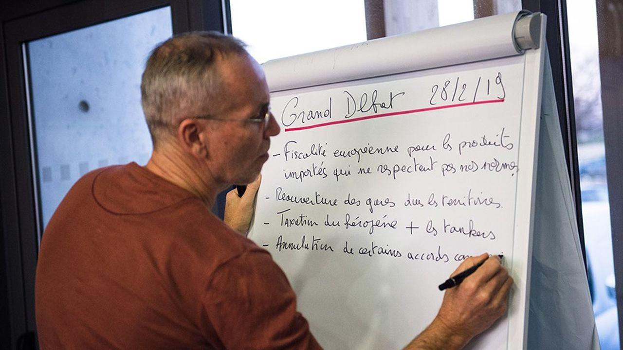 Dans le Vauluse, un modérateur du grand débat national rédige sur un tableau les propositions des citoyens.