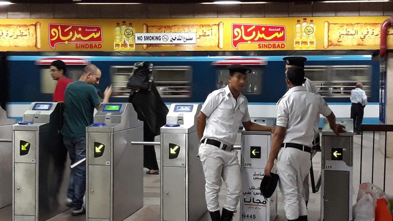 Les fonctionnaires égyptiens sont en surnombre. Pour garder les bornes d'entrée d'une station de métro du Caire, il faut au moins trois policiers.