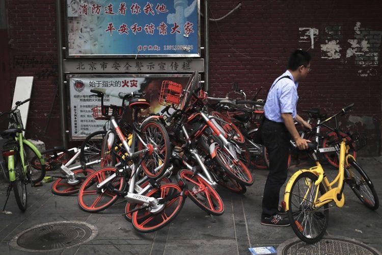 Un homme emprunte un vélo Ofo devant une pile de vélos Mobike.
