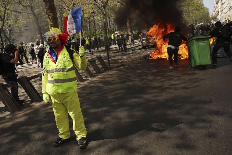 Un manifestant brandit un drapeau français tandis que des feux ont été allumés sur la voie publique à Paris.