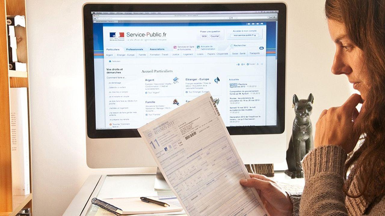 Site web service-public.fr. Declaration de revenus 2011 en ligne. Jeune femme avec formulaire papier devant ecran d'ordinateur service public, e administration, eadministration