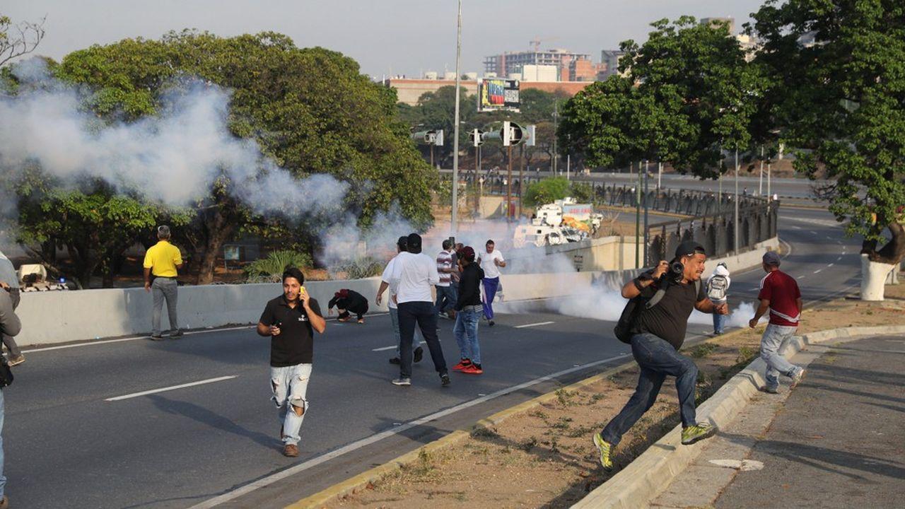 Des partisans de Juan Guaido cherchent un abri après des tirs de gaz lacrymogènes de la police près de la base militaire deLa Carlota, à Caracas.