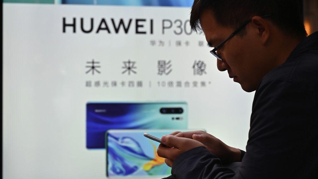 Un homme regarde son smartphone juste à côté d'une publicité pour Huawei à Shanghai, le 10mai 2019.