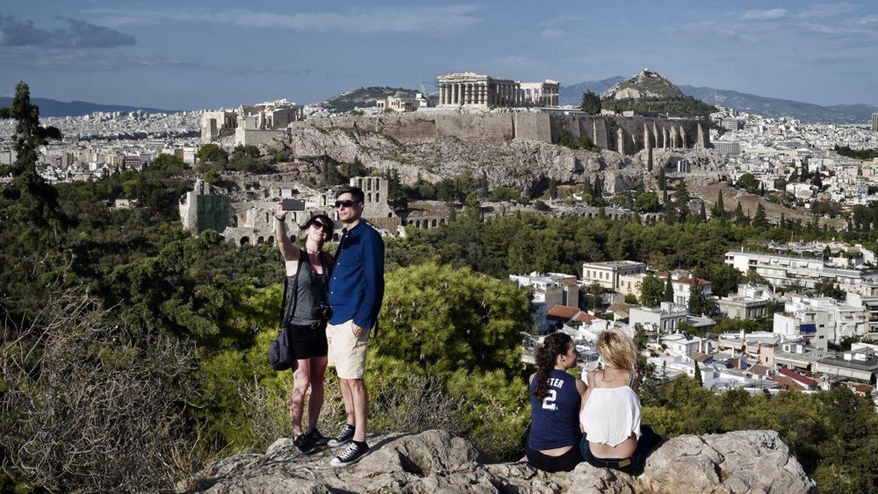 Des touristes prenant un selfie devant l'Acropole, en Grèce.