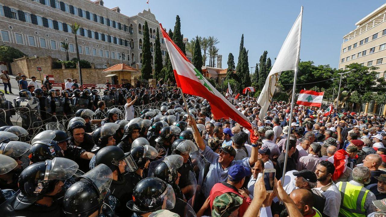 Des policiers ont fait face lundi à Beyrouth à des militaires en retraite qui essayaient d'entrer dans le Grand Serail, le siège du gouvernement. Les anciens militaires protestent contre une réduction de leur pension. (Photo by Marwan TAHTAH/AFP)