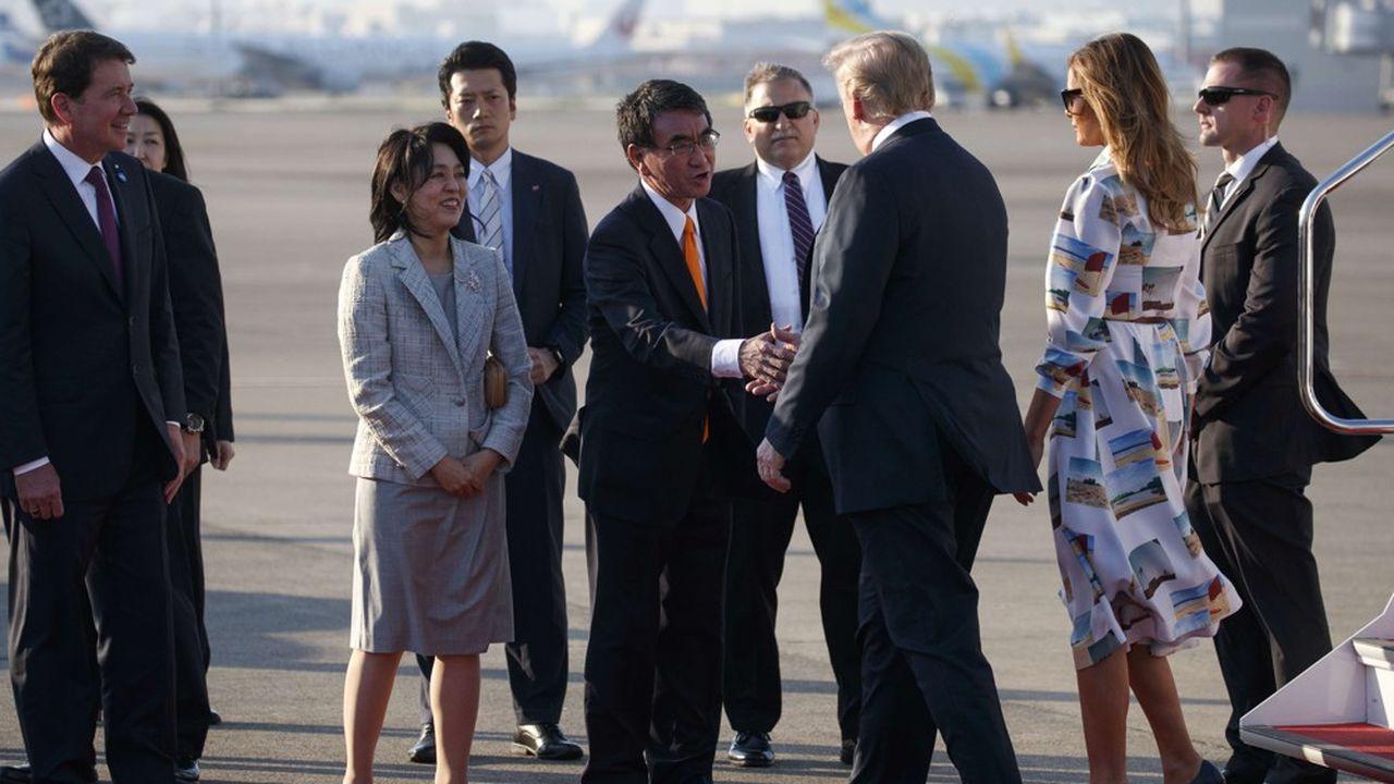 Donald Trump salue le ministre des Affaires étrangères japonais Taro Kono à son arrivée à l'aéroport international d'Haneda, à Tokyo.