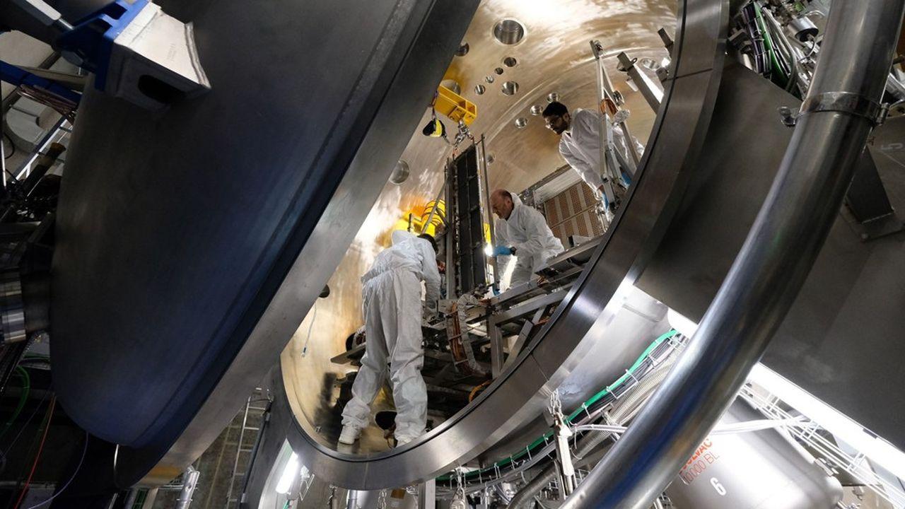 Des ouvriers posent une pièce de contrôle au coeur du futur réacteur.