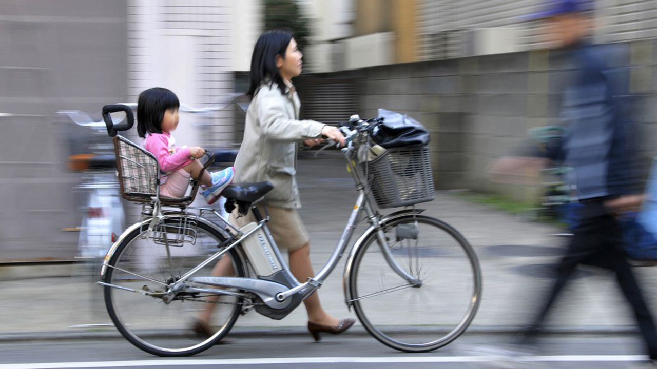 JAPAN-EDUCATION-SOCIETY-CHILDREN, FEATURE, BY MIWA SUZUKI A mother pushes her bicycle carrying her daughter she picked up from a nursery school in Tokyo on March 19, 2010. Parents known as 'monsters' for their aberrant demands have been pushing nursery and school workers over the edge, so much so that some teachers killed themselves, in a nation with one of the world's lowest birthrates. AFP PHOTO / Yoshikazu TSUNO (Photo by YOSHIKAZU TSUNO / AFP)
