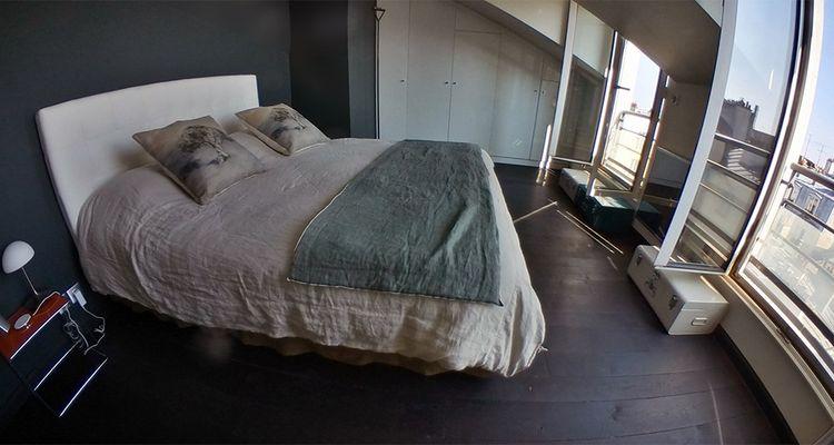 Le 6e étage donne sur une chambre avec parquet au sol et deux fenêtres donnant sur rue.