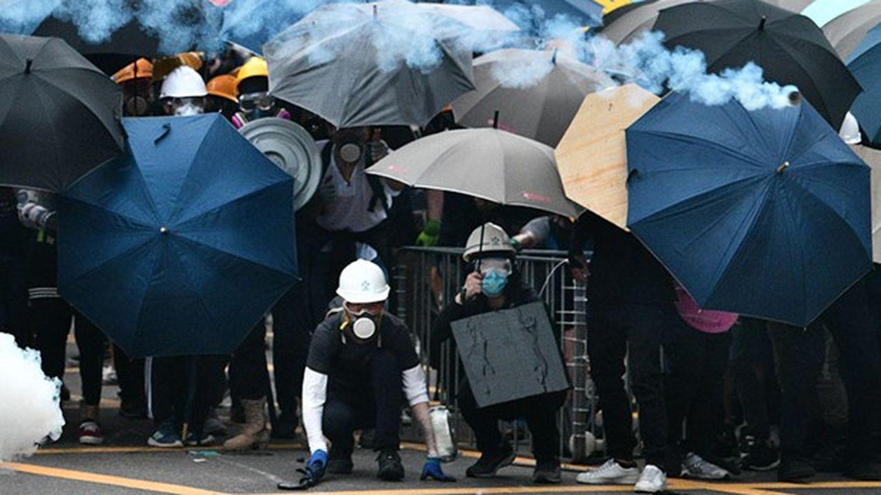 Les manifestants utilisent des parapluies pour se protéger des jets de gaz au poivre. Outre les masques et les lunettes, ils se couvrent également les membres de film plastique pour éviter les irritations provoquées par des substances envoyées par la police.