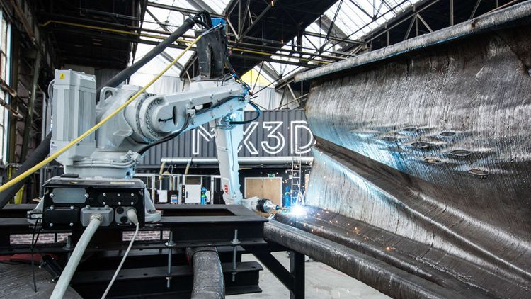 L'imprimante 3Dà six axes de MX3D était censée imprimer le pont sur site, en commençant par les appuis structurels et en poursuivant par la passerelle au-dessus d'un canal d'Amsterdam. Mais cela s'est révélé trop compliqué et il a finalementété imprimé en usine.
