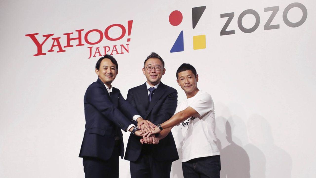 Yusaku Maezawa (à droite), le milliardaire japonais fondateur du site de vente en ligne de vêtements Zozo, numéro un au Japon, scelle l'accord de vente à Yahoo! Japan avec son directeur général, Kentaro Kawabe (à gauche) et le nouveau directeur général de Zozo, Kotaro Sawada.