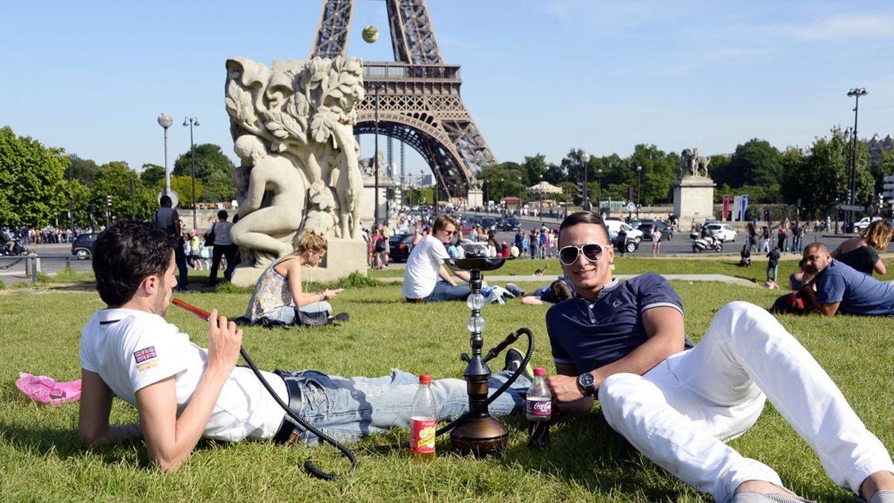 A Paris, de jeunes fumeurs de narguilé devant la tour Eiffel.