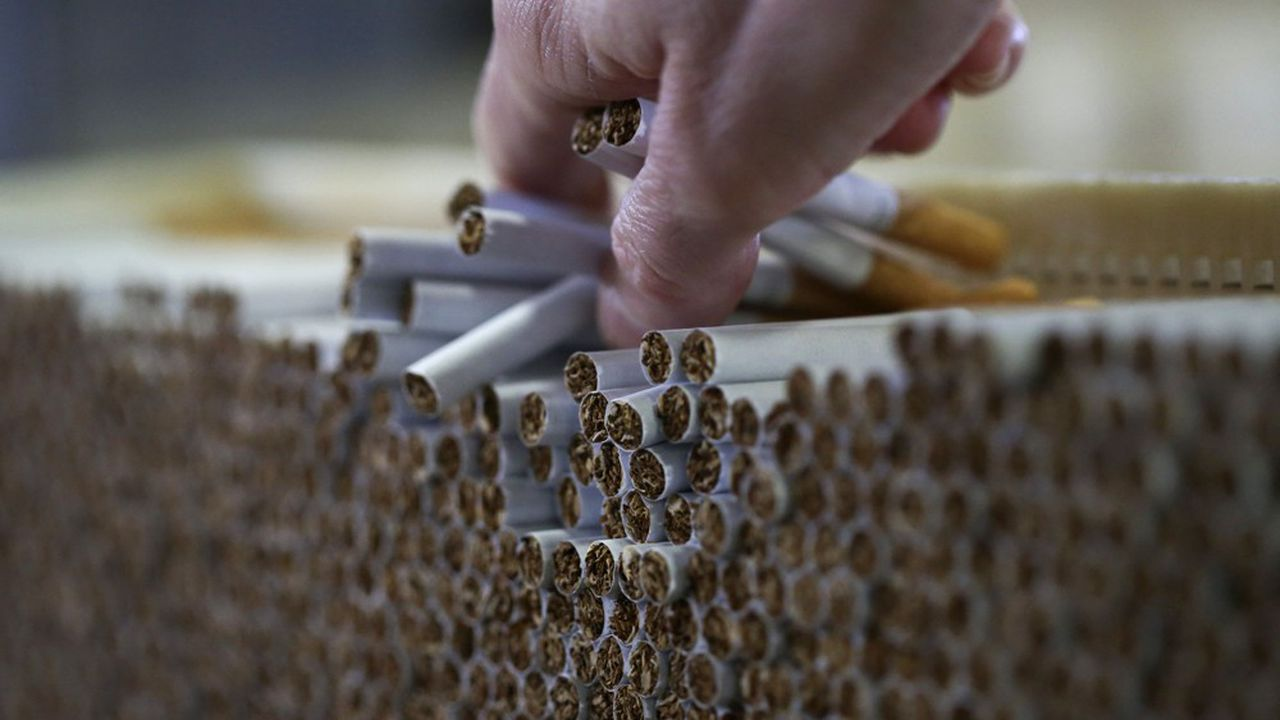 An employee checks cigarettes during production in the U.K. Photographer: Chris Ratcliffe/Bloomberg