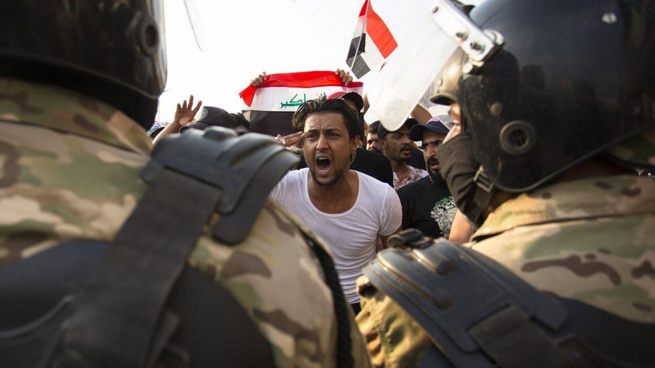 Unmanifestant interpelle les forces de l'ordre lors d'un défilé protestant contre la corruption, le chômage et la médiocrité des services publics, à Bagdad.