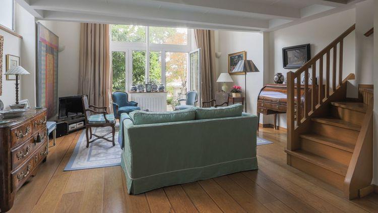 Orientés plein Est, le salon et la salle à manger d'une surface de plus de 35 m² disposent de grandes portes-fenêtres donnant sur une terrasse dallée de pierres avec un jardin en contrebas.