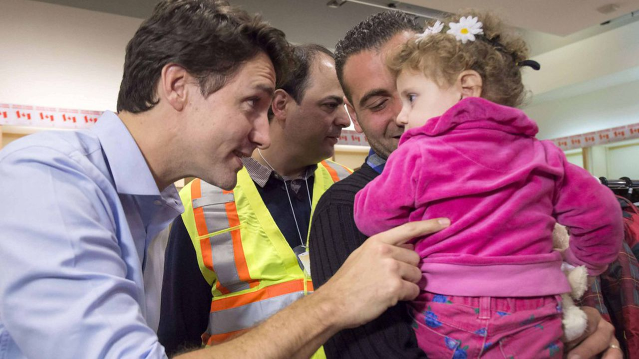 Prime Minister Justin Trudeau, left, greets Madeleine Jamkossian, right, and her father Kevork Jamkossian, refugees fleeing the Syria, during their arrival at Pearson International airport, in Toronto, on Friday, Dec. 11, 2015. The first Canadian government plane carrying Syrian refugees arrived in Toronto late Thursday. (Nathan Denette/The Canadian Press via AP) MANDATORY CREDIT/NSD605/944118459854/MANDATORY CREDIT/1512111107