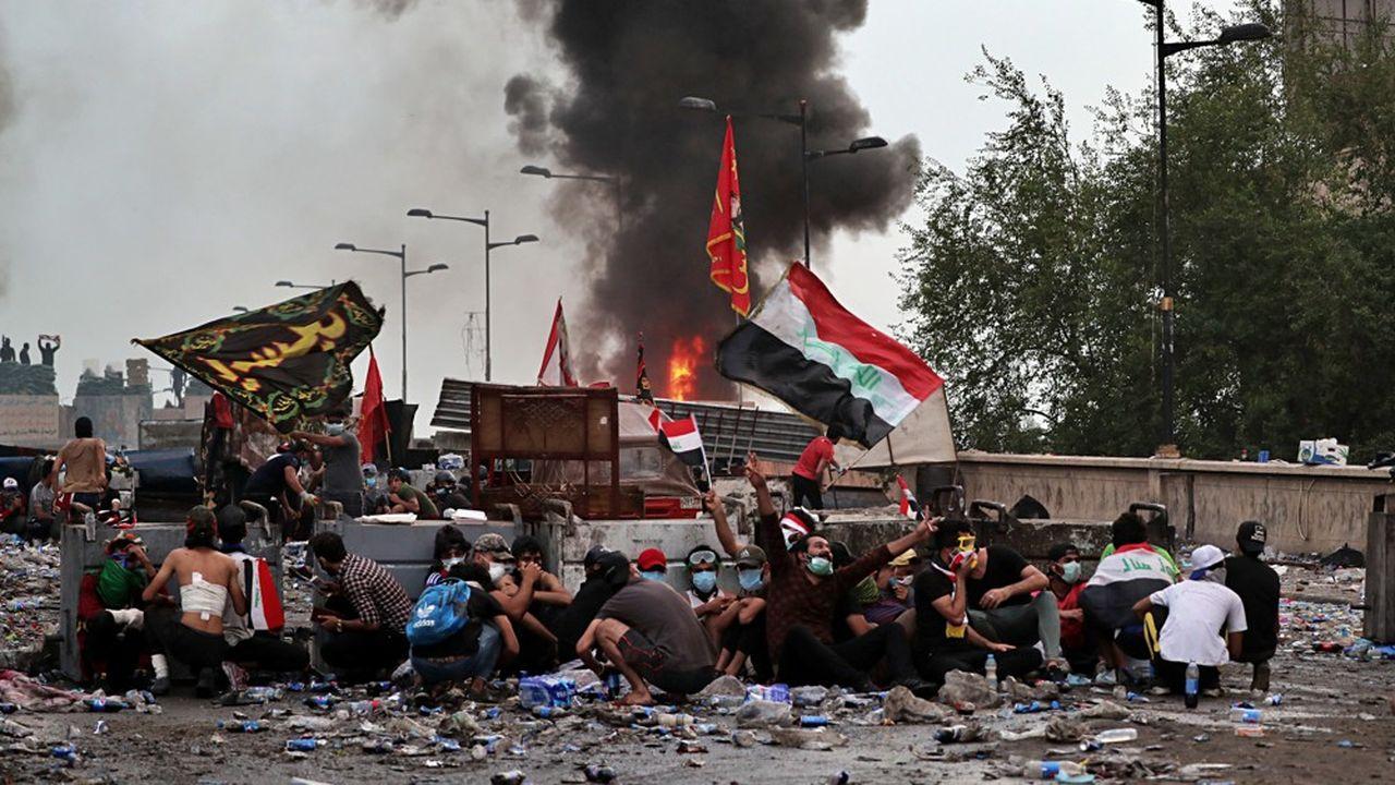 Des manifestants se mettent à l'abri à Bagdad ce lundi après des tirs des forces de sécurité.