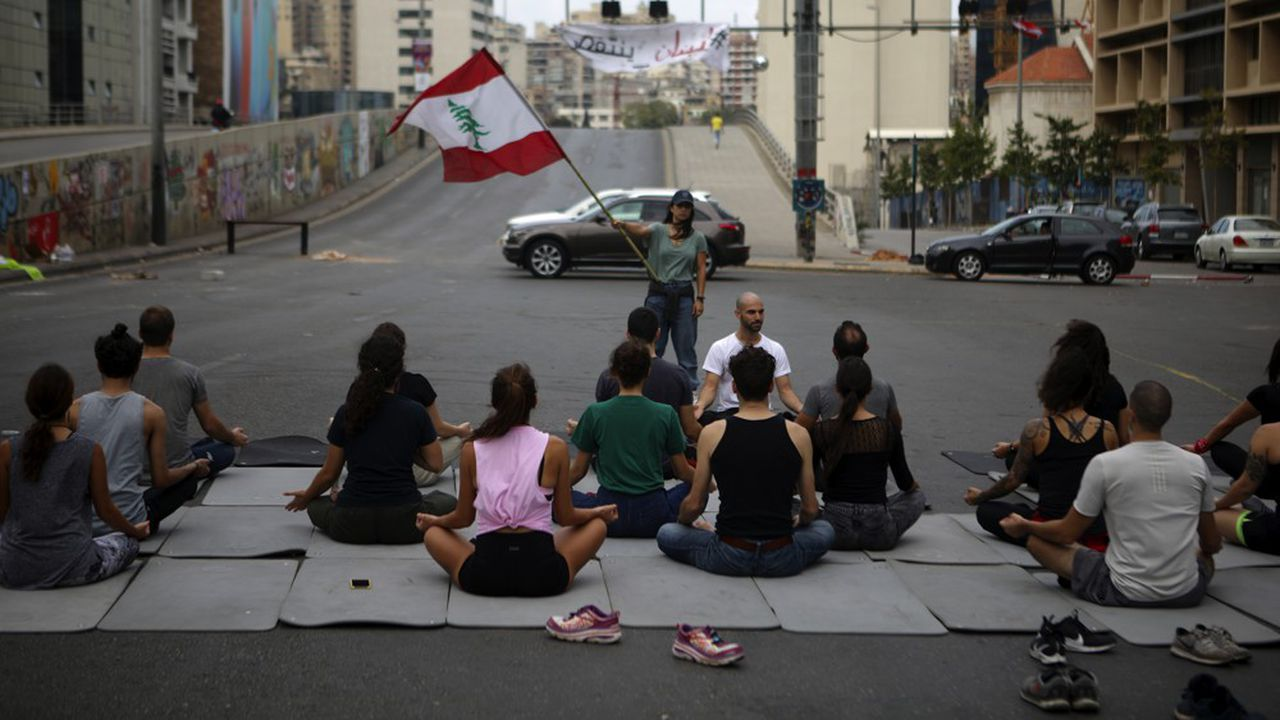 Des manifestants pratiquent le yoga pour se relaxer dans une avenue bloquée de Beyrouth, où des contre manifestants ont attaqué les cortèges et les barricades.