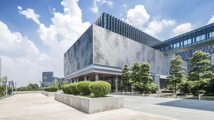 La façade baptisée « E+C- », composée d'écailles d'aluminium mobiles bougeant sous l'effet du vent et de la pluie transforme le mouvement en électricité.