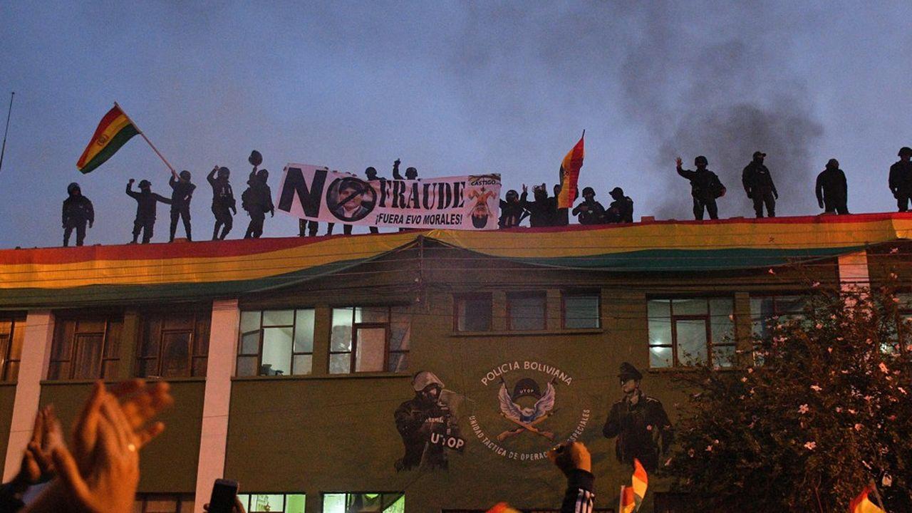 Des images diffusées en direct à la télévision ont montré une vingtaine de policiers grimpant au sommet du bâtiment du quartier général de la police de Cochabamba en agitant le drapeau bolivien, tandis que des dizaines de jeunes opposants les encourageaient depuis la rue.