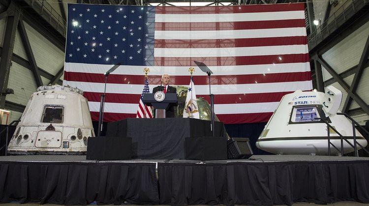 Le vice-président américain Mike Pence, en 2017, aux côtés des capsules Dragon (à gauche) et Starliner (à droite).