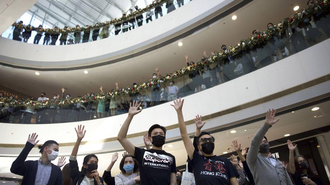 Dans le centre commercial IFC de Hong Kong, les manifestants lèvent la main pour symboliser les cinq demandes qu'ils revendiquent.