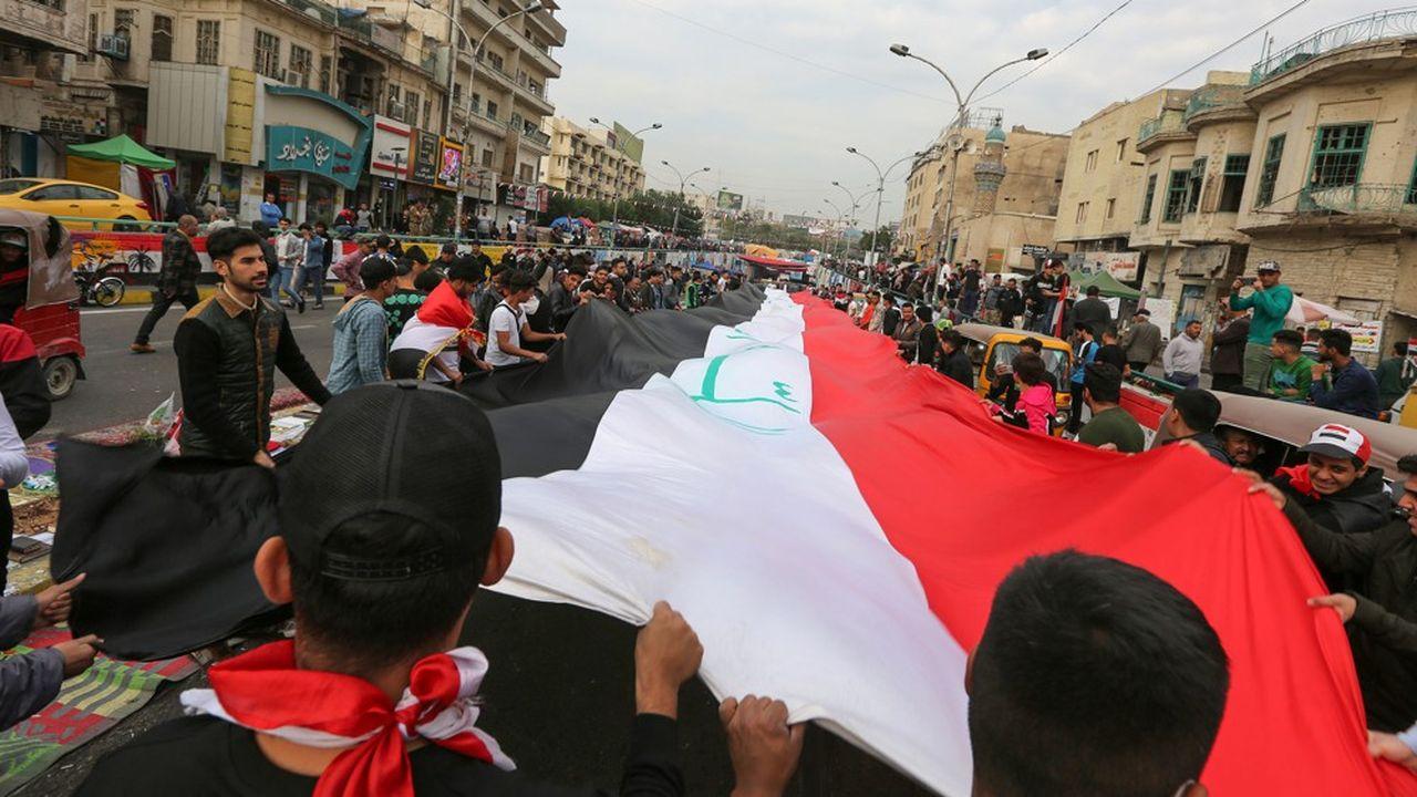 Des manifestants déploient le drapeau national sur la place Tahrir à Bagdad, deuxième capitale du monde arabe, l'épicentre du soulèvement contre le pouvoir. Photo par SABAH ARAR/AFP)