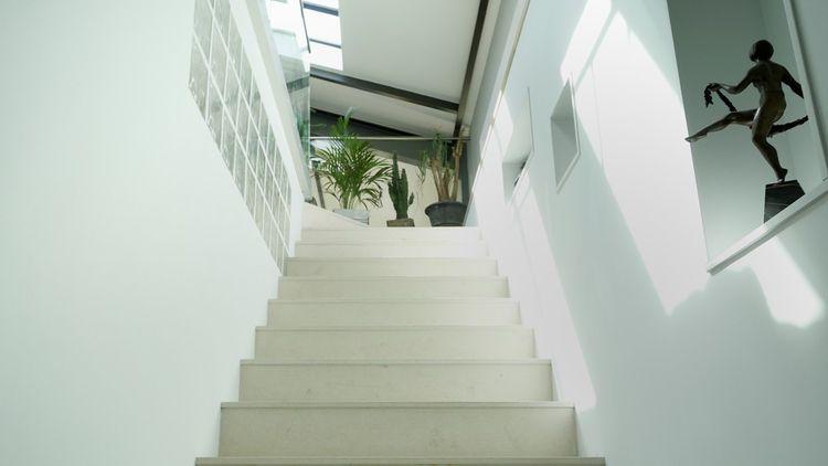 Ce grand escalier mène à ce loft qui occupe tout le premier niveau de cette maison
