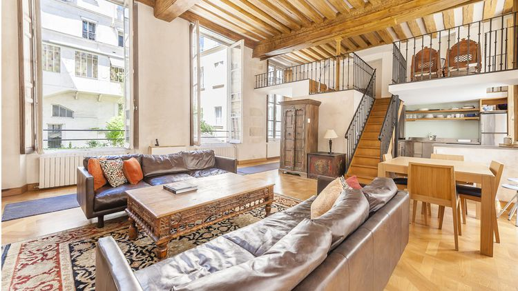 Le salon de 37,50 m² offre 4 mètres de hauteurs sous plafond avec une vue sur la cour.
