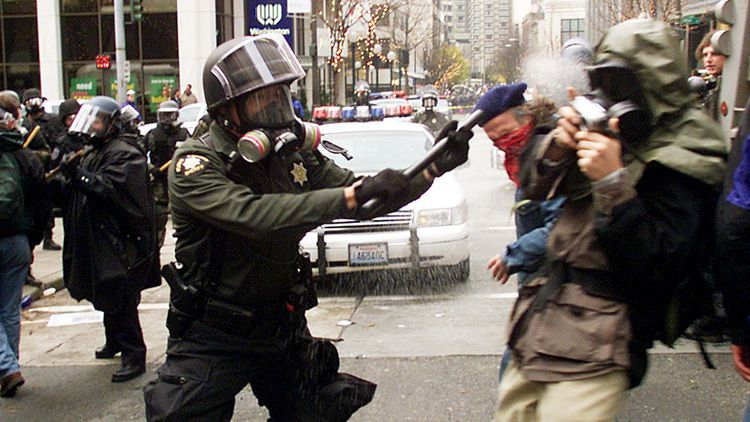 A Seattle, un violent clash entre la police antiémeutes et des manifestants altermondialistes, le 30 novembre 1999, devant le Washington State Convention Center où se tenait le sommet de l'OMC.
