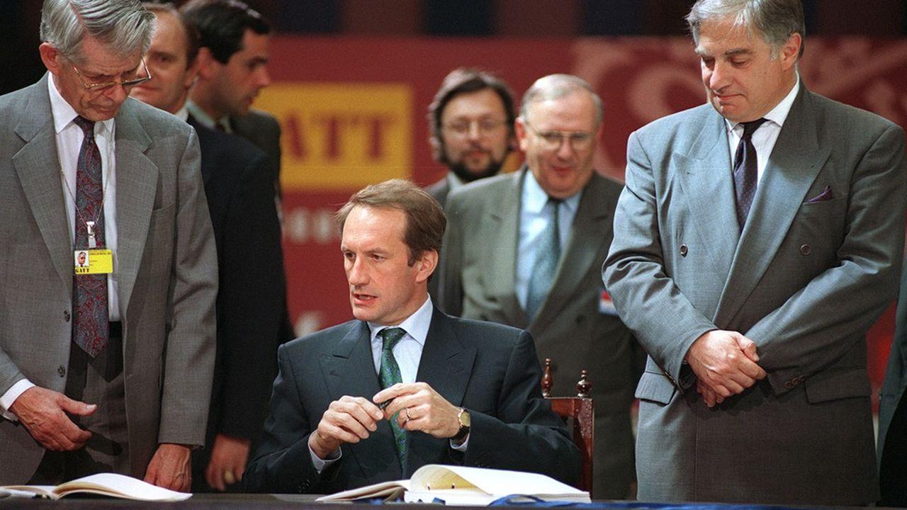Le ministre français du Commerce et de l'Industrie, Gérard Longuet, avec à ses côtés le directeur général du GATT, Peter Sutherland (à droite) signe, le 15avril 1994 à Marrakech, la naissance de l'OMC.