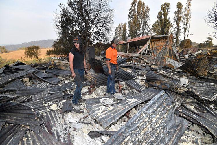 Des Australiens photographiés le 8janvier dans les ruines calcinées de leur maison à Batlow.